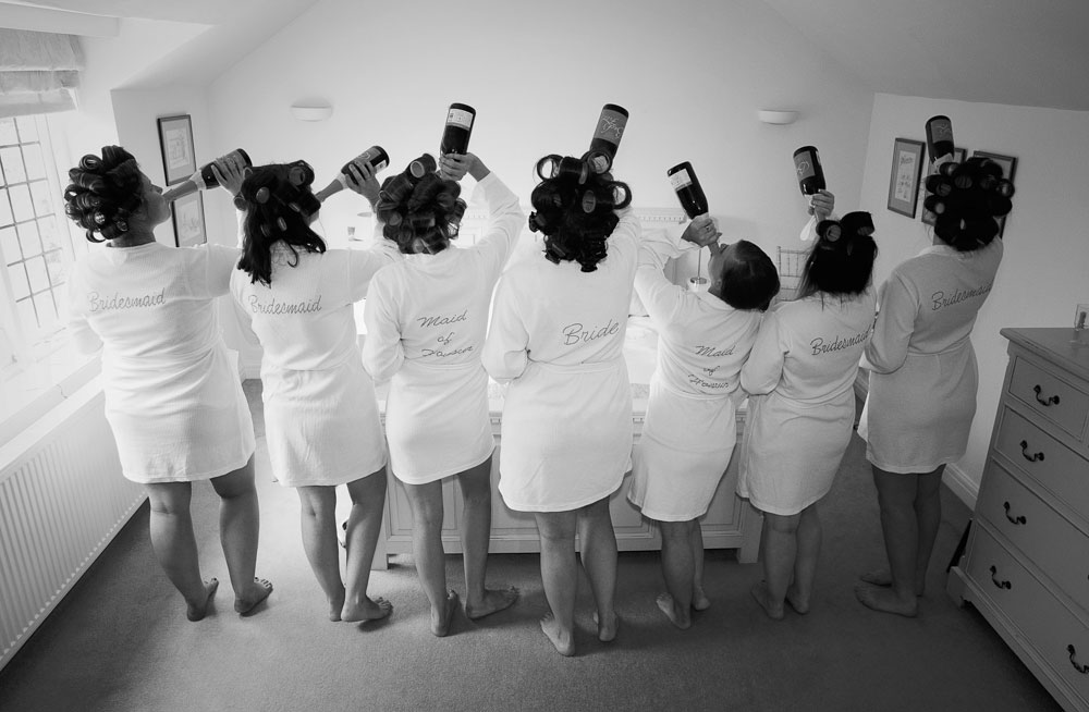 Fun bridal party photo drinking champagne with hair curlers