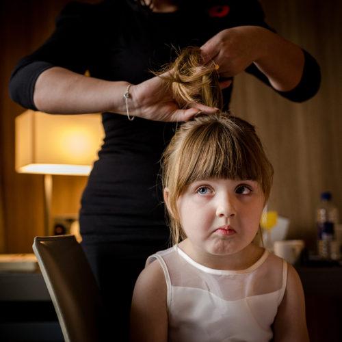 Little flower girl having her hair done