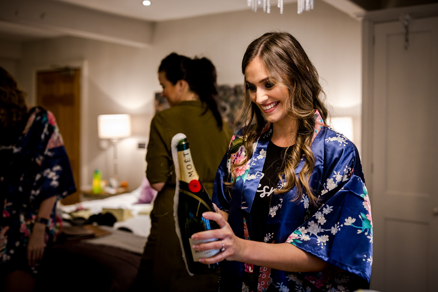 Bridesmaid opening Champagne during a winter wedding at Stanley House