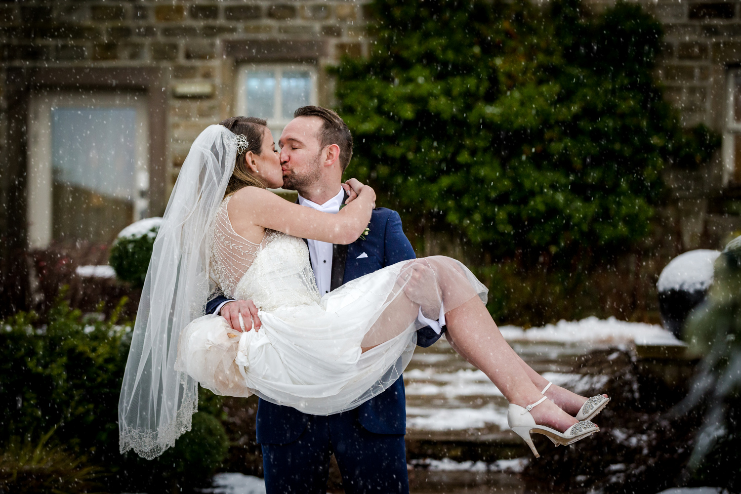 The groom picks up his bride during this snowy wedding at Stanley House Hotel in Clitheroe