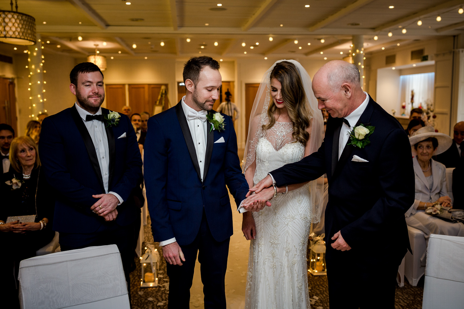 The father of the bride gives his daughters hand to the groom at Stanley House