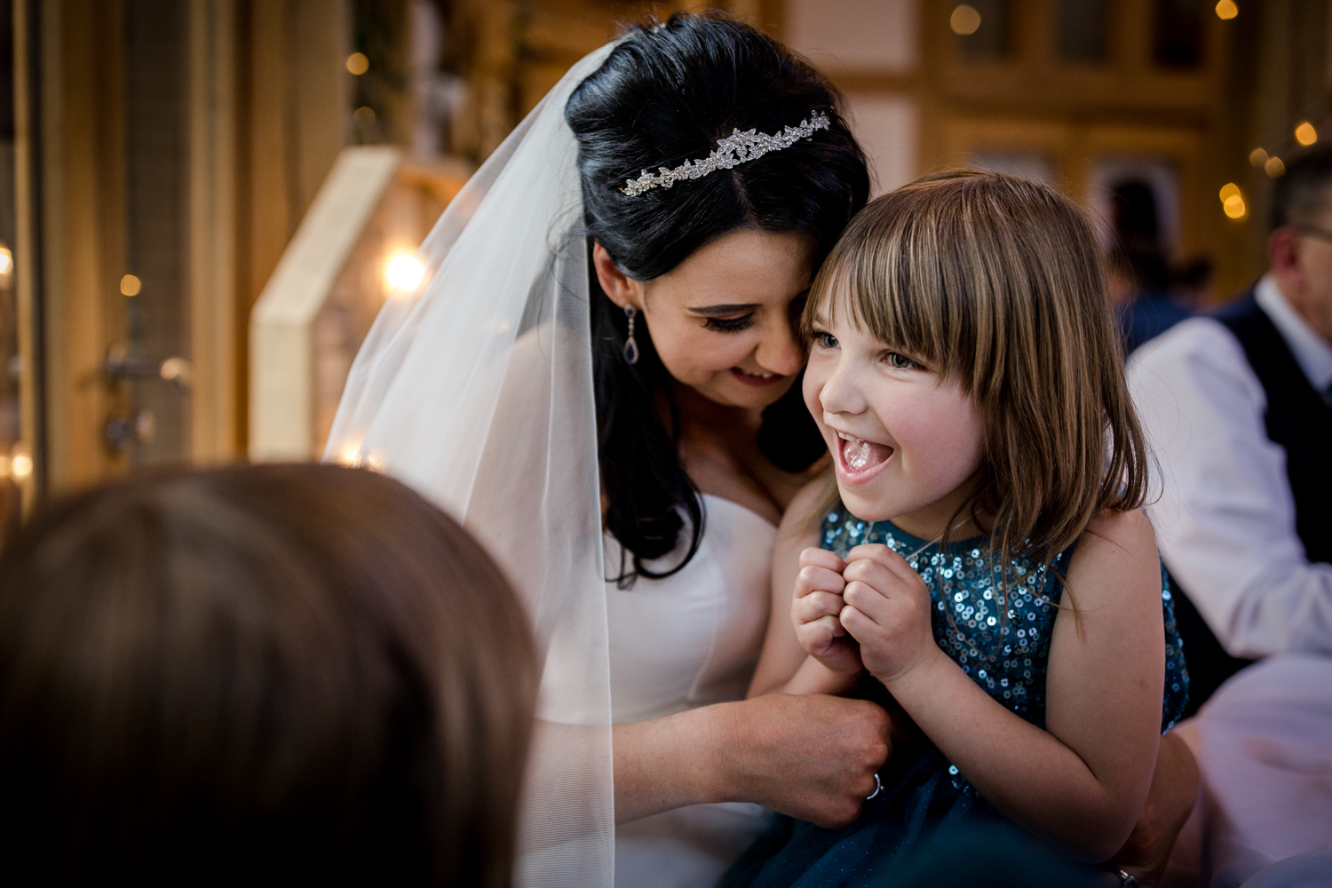 Flower girl cuddles during an Oak Tree Peover Wedding in Cheshire