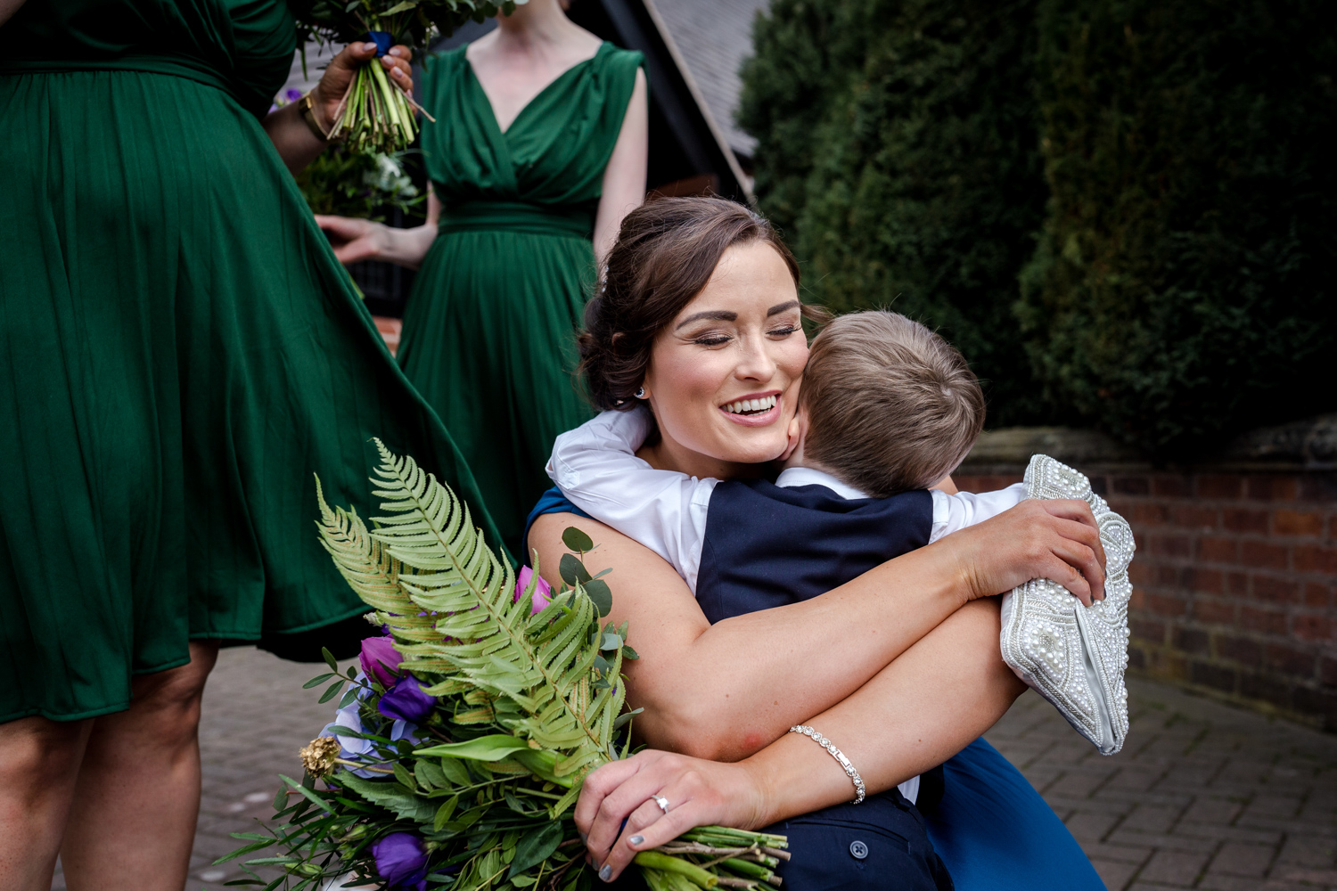 Bridesmaid hugs outside St Marys Church in Middlewich
