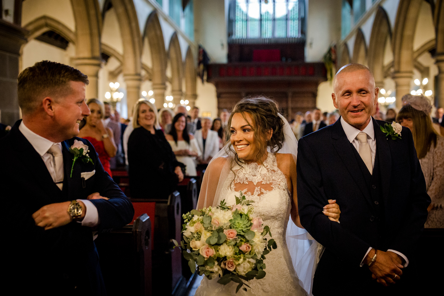 The bride is walked down the aisle by her dad