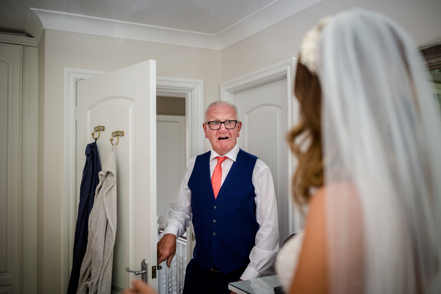 Father of the bride sees his daughter in her wedding dress for the first time