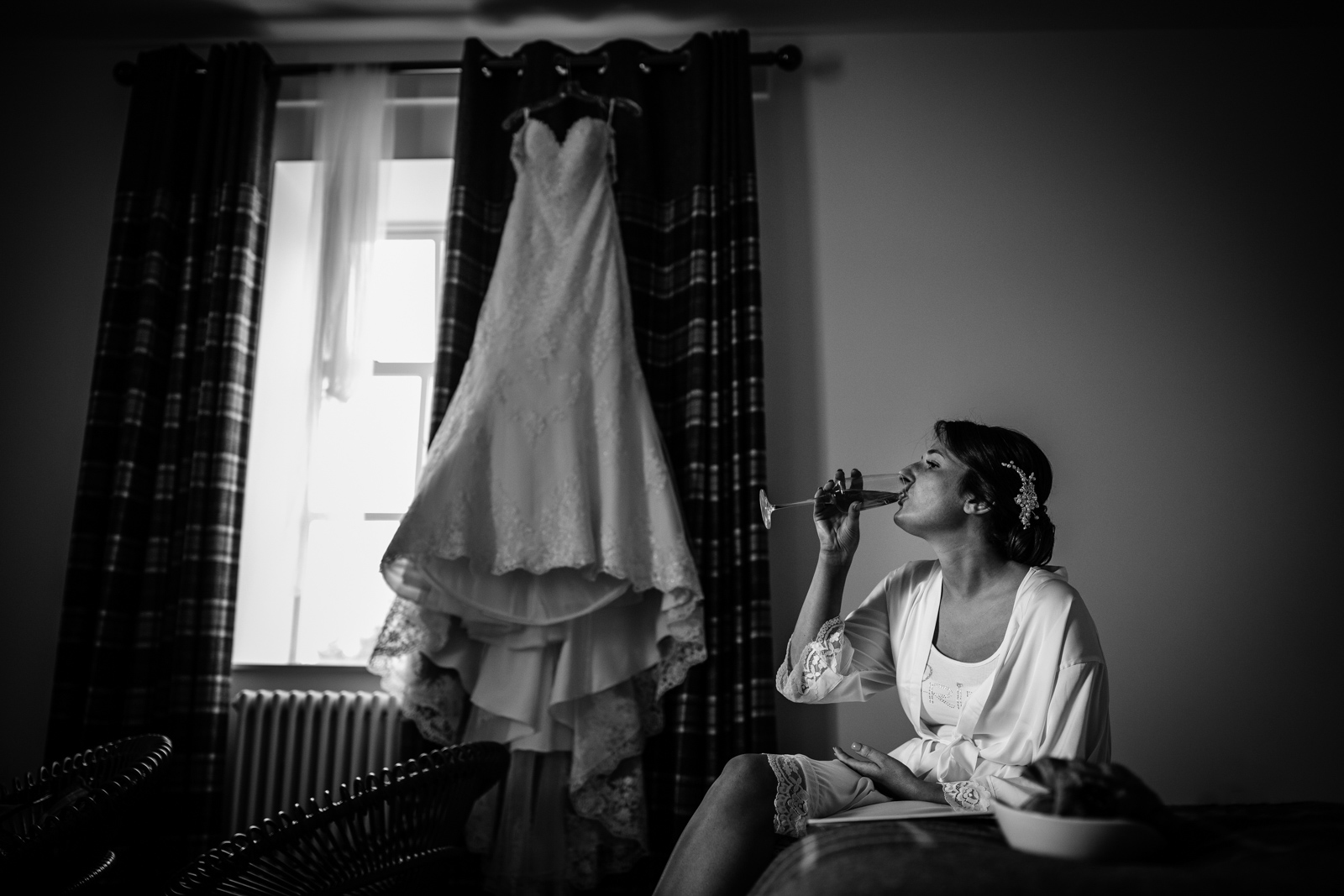 bride drinking champagne on the morning of her wedding with wedding dress hanging up in the background