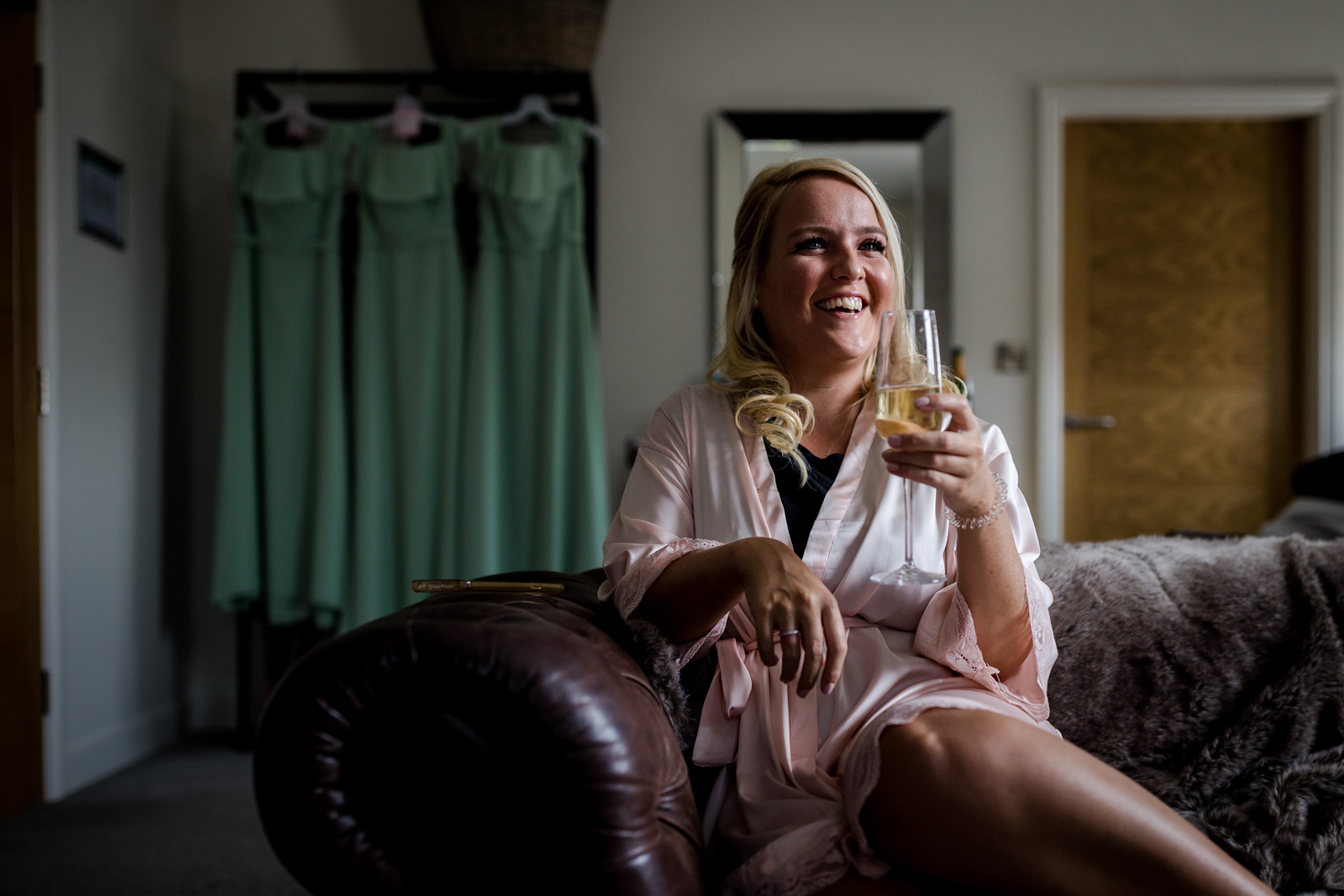 a bridesmaid drinking champagne with mint green bridesmaids dresses hanging in the background